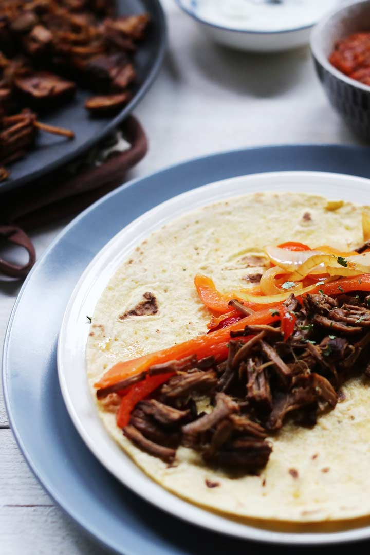 Shredded tender beef fajitas. Great Tex Mex dinner recipe made with slow cooked beef. Want to make this recipe visit thetortillachannel.com #beeffajitas #fajitas #slowcookedrecipe #fajitasrecipe