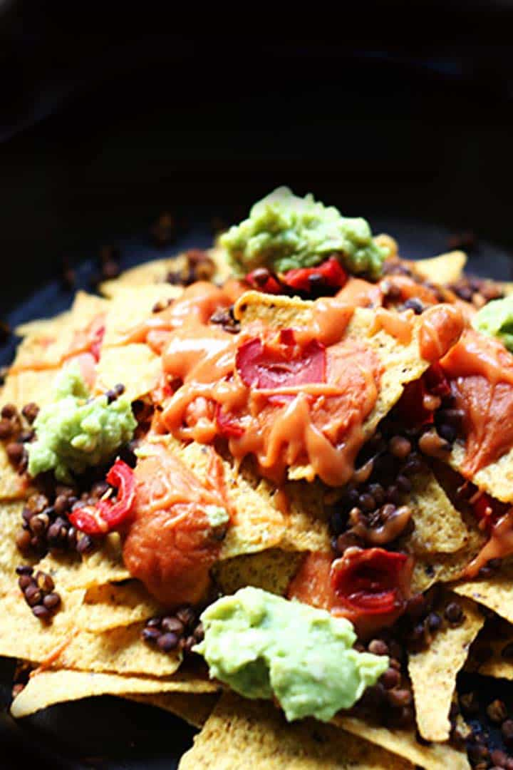 The ultimate vegan lentils nachos with guacamole and salsa. Such a delicious snack. Visit thetortillachannel.com for the instructions and video. #nachos #vegannachos #ultimatenachos #lentilsnachos #snack
