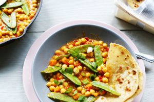 Yummy yellow chickpea curry overhead skillet and flatbread