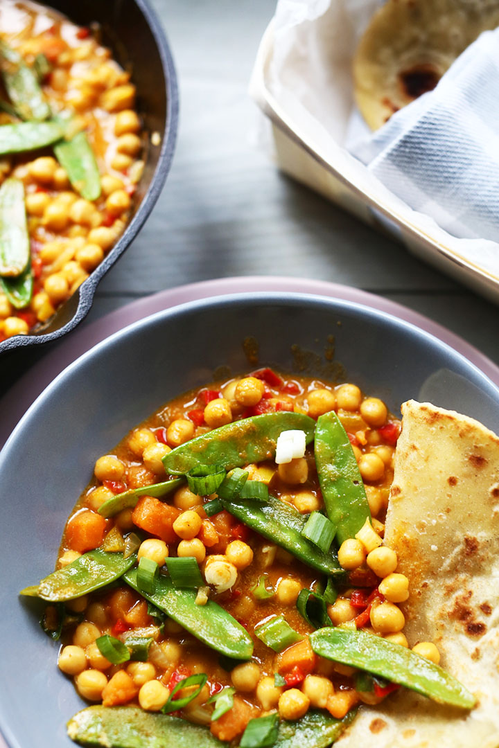 Yummy yellow chickpea curry portrait overhead with flatbread