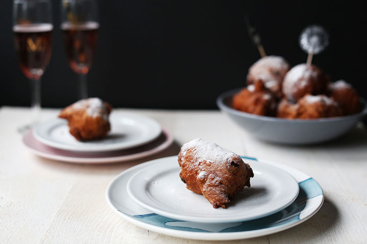 Dutch traditional oliebollen two on a plate and two glasses of pink champagne