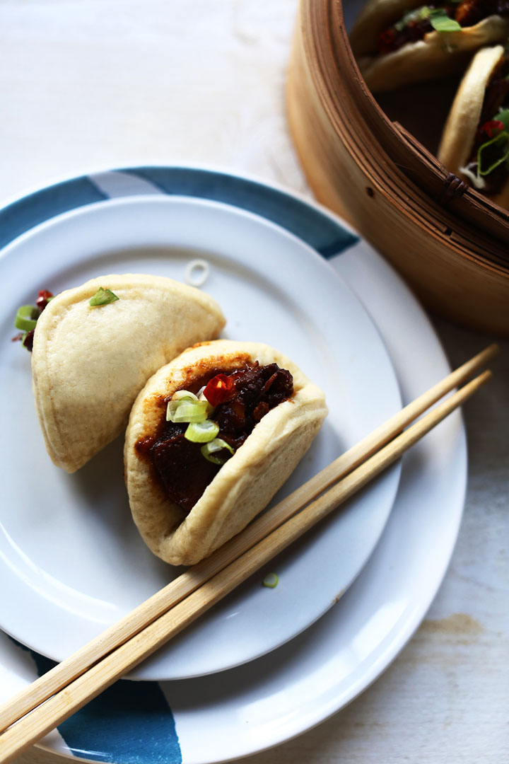 Spicy soy pork with steamed buns on plate overhead