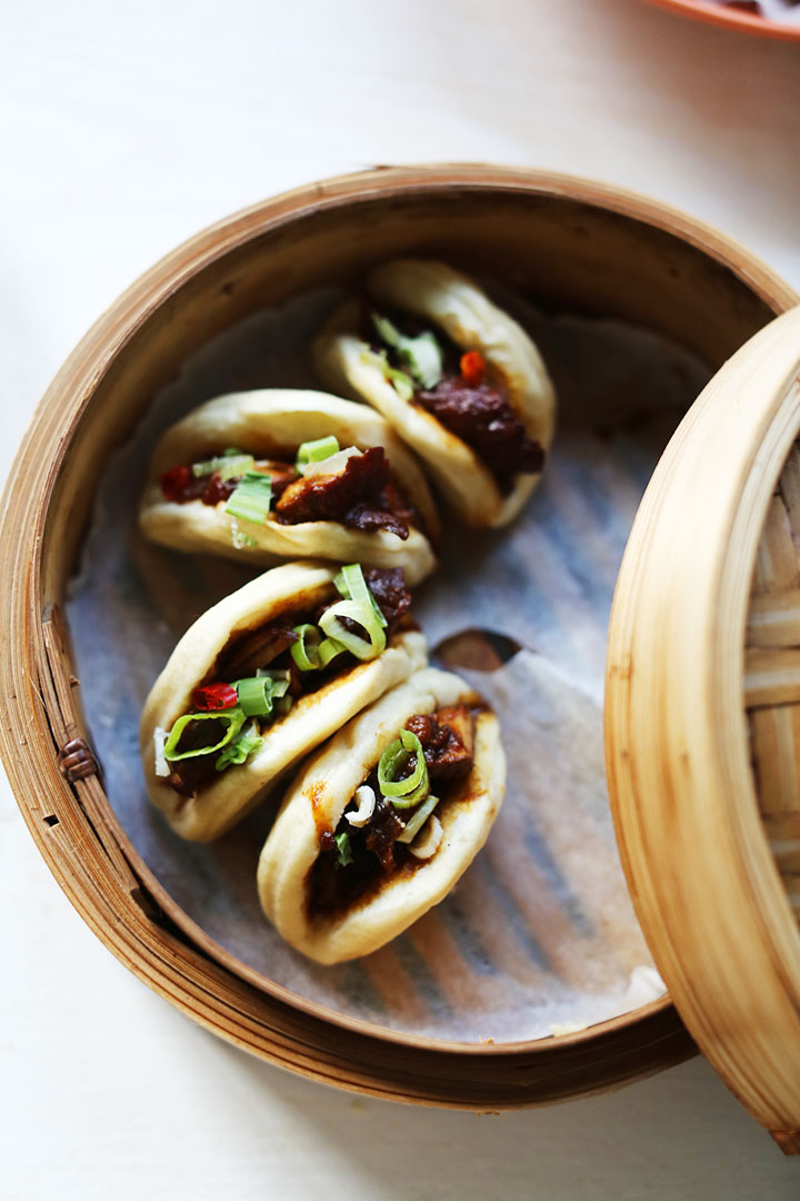 Spicy soy pork with steamed buns half filled steamer portrait