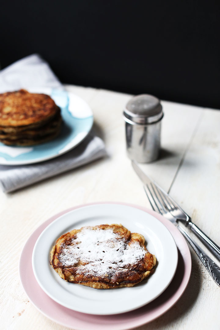 Fluffy banana coconut stacked one pancake with icing sugar and stack of pancakes