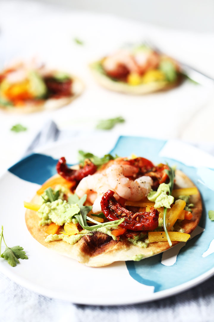 Avocado shrimp tostada. Made with pan-fried tortilla, quacamole, bell pepper, sun-dried tomato, shrimp and rucola. Healthy fish tostada is a favorite lunch recipe. Visit the website for the (video) instruction.