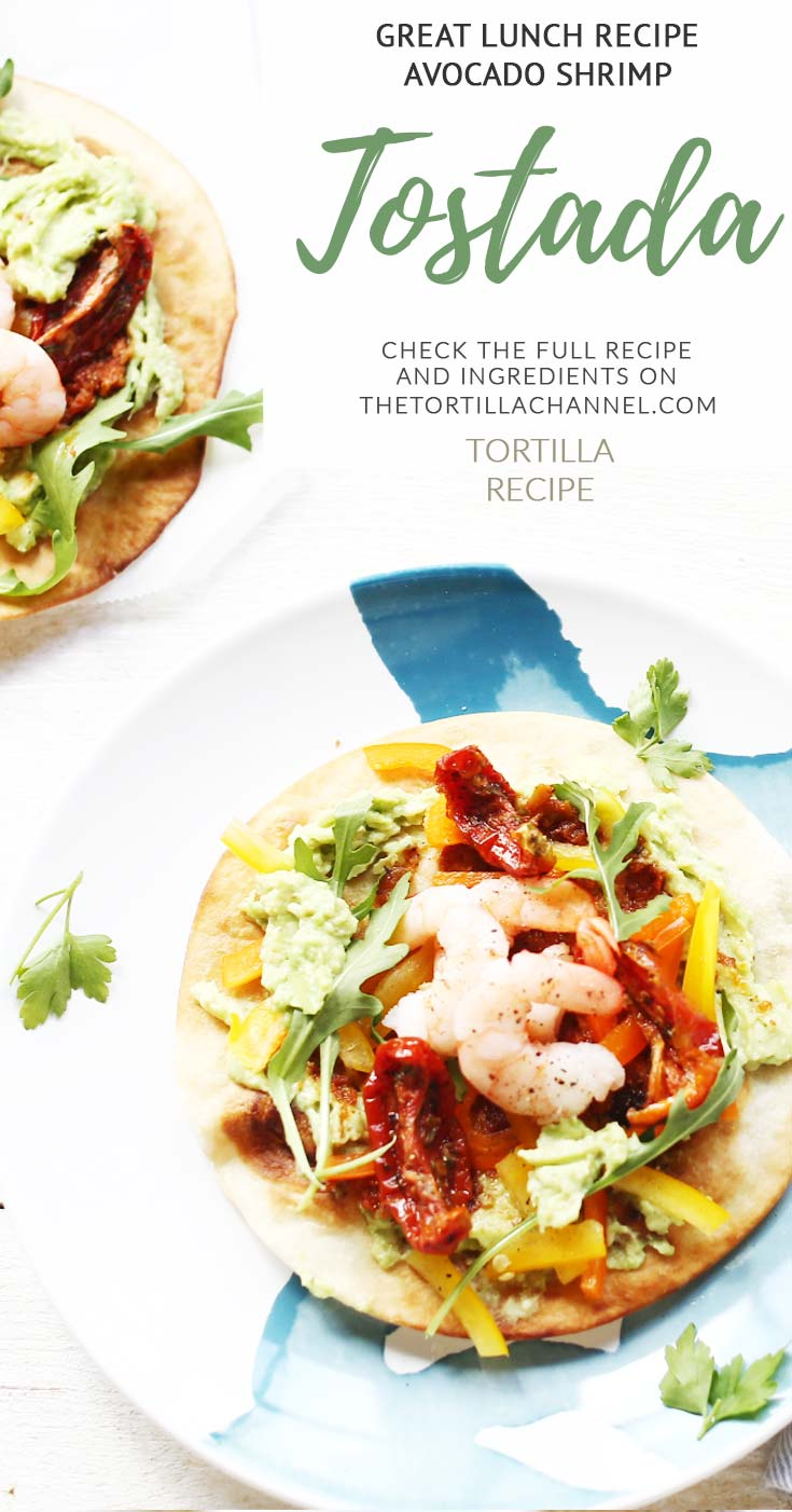 Avocado shrimp tostada. Made with pan-fried tortilla, quacamole, bell pepper, sun-dried tomato, shrip and rucola. Healthy fish tostada is a favorite lunch recipe. Visit the website for the (video) instruction.