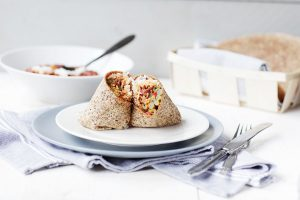 Vegan lentil Chili burrito on a plate. Lentil stew recipe. Delicious and easy. Visit the website or pin it now.
