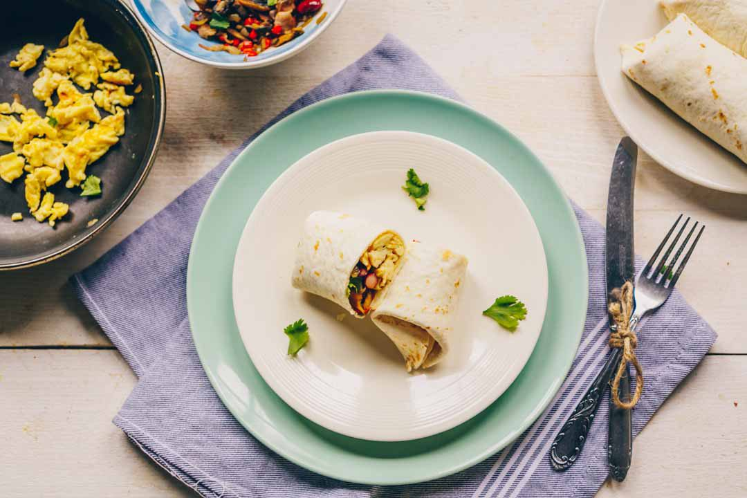 The best breakfast burrito made with scrambled eggs, vegetable mix, bacon and kidney beans. Wrapped in a tortilla this burrito is freezer friendly and easy to make. Visit thetortillachannel.com for the full recipe and recipe. #thetortilachannel #breakfastburrito #breakfastburritorecipe #burritorecipe #burritos #breakfast #tortillarecipe