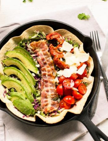 Avocado tomato salad in an oven baked tortilla bowl. Add some bacon, sunflower seeds and parmesan cheese.