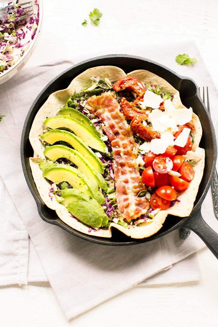 Great avocado tomato salad with lettuce, sun dried tomatoes, bacon, parmesan cheese and avocado. Visit thetortillachannel.com for this recipe #avocado #tortillasalad #salad #summersalad #avocadotomatosalad.