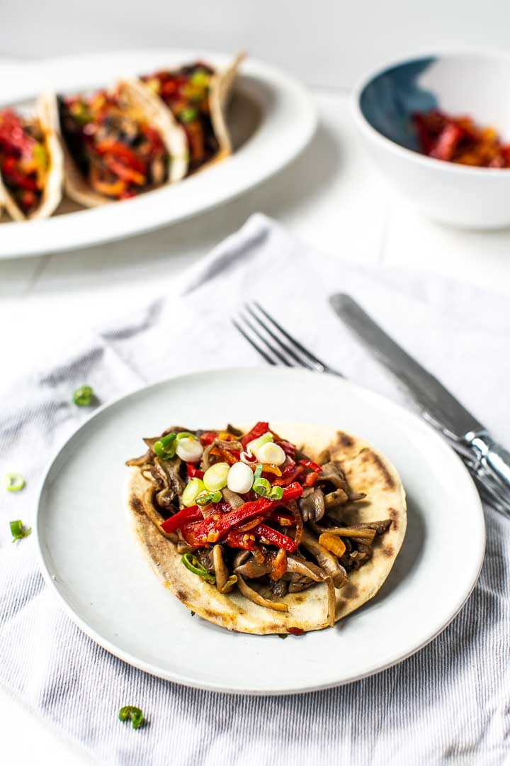 Vegan mushroom fajitas made with white and oyster mushrooms and the best homemade fajitas seasoning. Visit thetortillachannel.com for the recipe and video #veganfajitas #mushroomfajitas #oystermushroomfajitas #fajitasrecipe