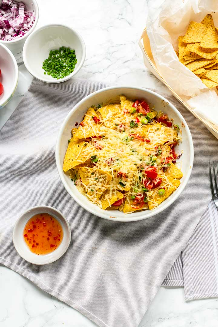 Healthy vegetarian nachos with nachos, red onions, tomatoes, jalapeno and cheese, lot of cheese. This delicious snack is done in less than 10 minutes. Visit thetortillachannel.com for the full recipe. #tastynachos #vegetariannachos #easynachos #nachosnack #simplenachossnack