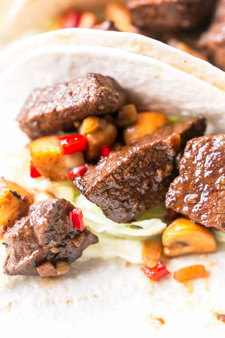 Mexican steak tacos or carne asada tacos are the best. Made with soft and tender steak bites. Wrapped in a soft tortilla and lots of vegetables. Visit thetortillachannel.com for the full recipe #thetortillachannel #mexicansteaktaco #steaktacos #tacorecipe