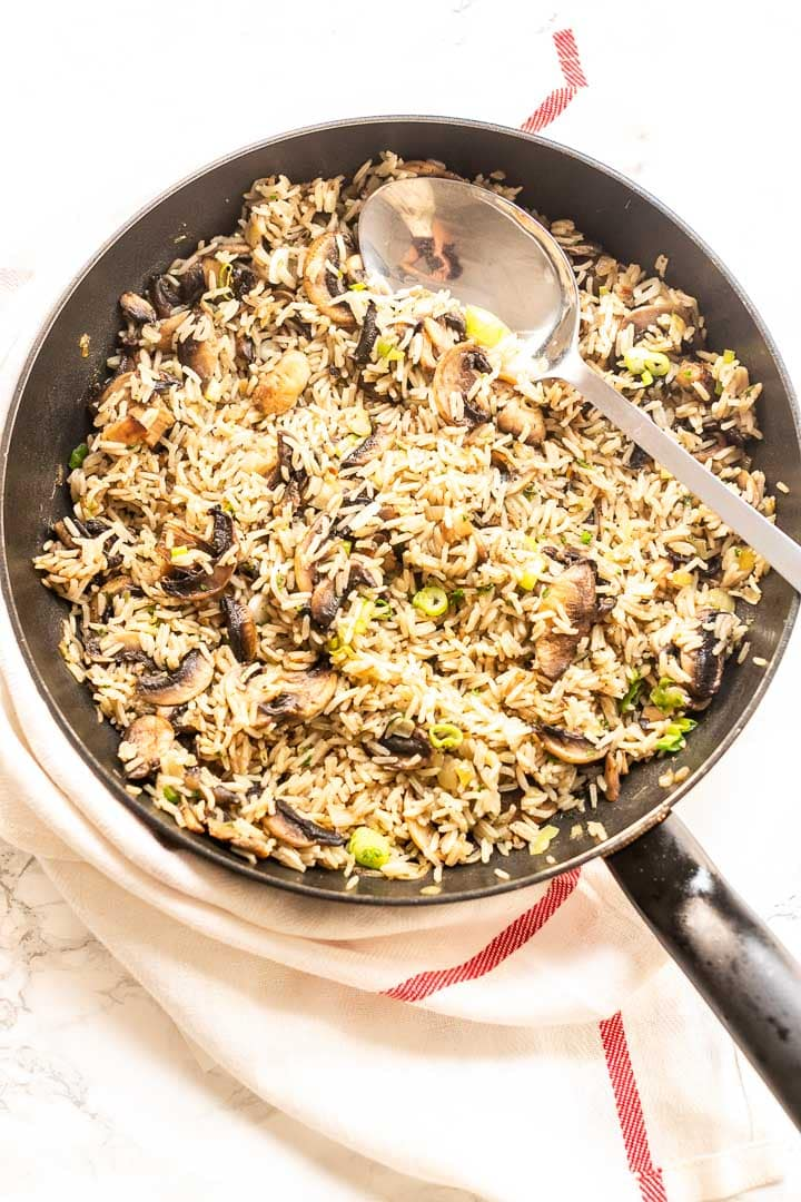 Mushroom rice is a super tasty side dish. This one pot recipe is vegan and made with vegetable broth and lots of vegetables. Visit thetortillachannel.com for the full recipe. #thetortillachannel #mushroomrice #sidedish #ricerecipe #easymushroomrecipe