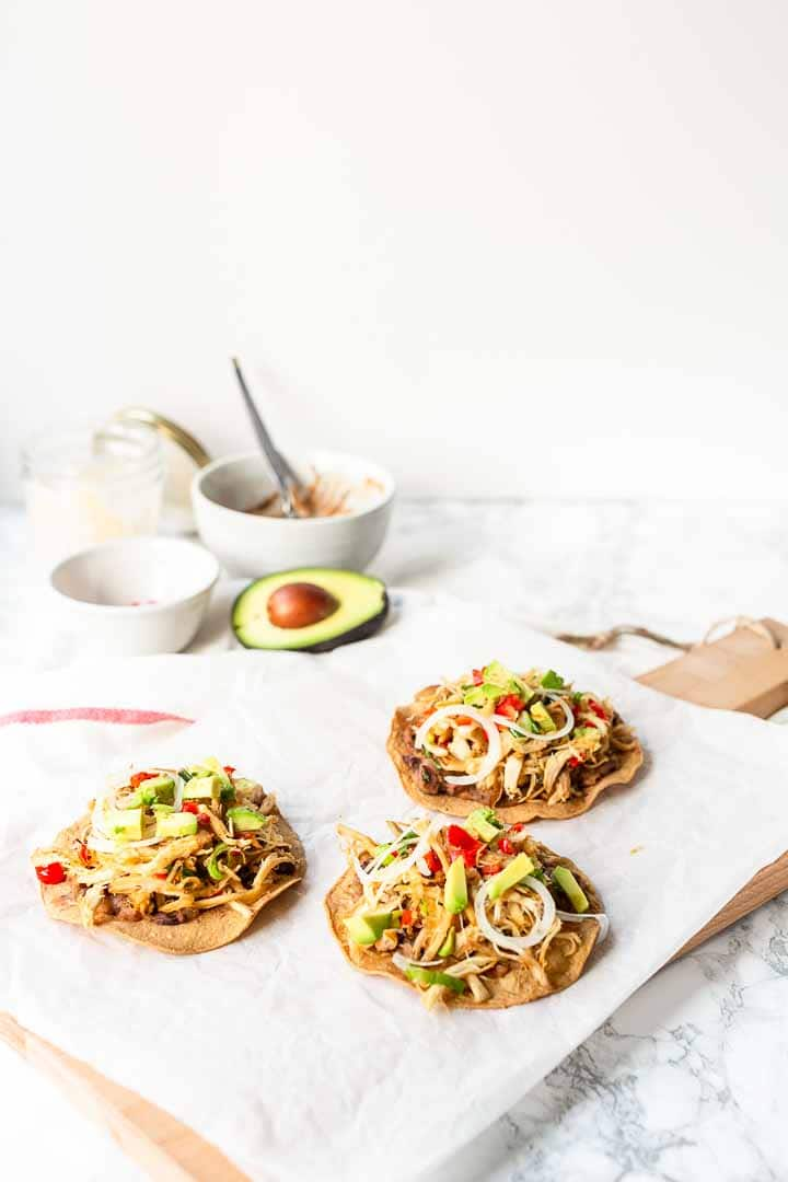 Looking for the best chicken tostadas? Try this slow cooked shredded chicken tostada recipe made with corn tortillas. Great for lunch or dinner. Visit thetortillachannel.com for the full recipe #thetortillachannel #chickentostada #rotisserichicken #tostadas #slowcookedchickentostadas