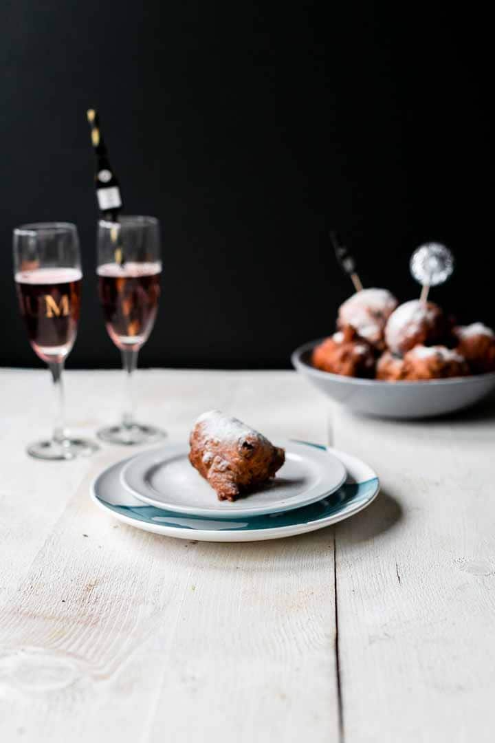 Looking for the best traditional oliebollen? Try this fried Dutch doughnut recipe. They are eaten hot, a little chewy and sweet. Decorate with icing sugar. Visit thetortillachannel.com for the full recipe + video #thetortillachannel #oliebollen #Dutchdoughnuts #Dutchdonuts #Dutchies #friedoliebollen #traditionaloliebollen
