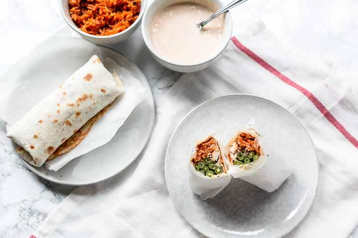 The best shredded chicken burrito recipe made with slow cooker whole chicken, Mexican rice and green beans. These burritos are easy to make. Chicken burritos are a great dinner. Visit thetortillachannel.com for the full recipe #thetortillachannel #shreddedchickenburrito #chickenburrito #burrito #slowcookchicken #dinner