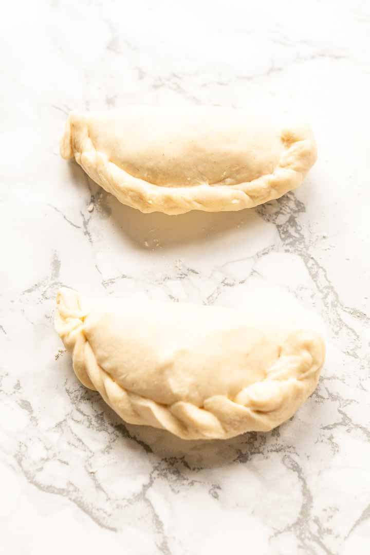 Tips and techniques how to fold and seal empanadas. There are a number of ways to crimp the edge of an empanada. You need some practice but lot of options. Visit thetortillachannel.com for all the options. #thetortillachannel #foldempanadas #empanadas #foldandsealempanadas #crimpedgesempanada