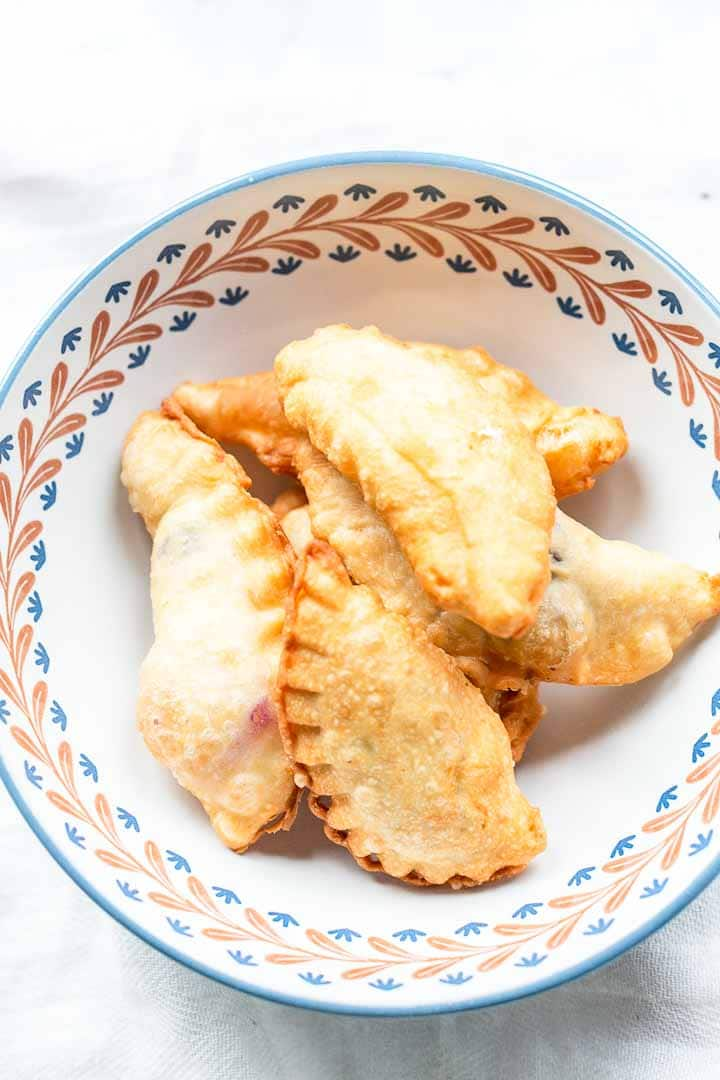 These dessert empanadas with blueberry are amazing. These fried empanadas are crunchy on the outside with a slightly sweet cream cheese filling. Visit thetortillachannel.com for the full recipe #thetortillachannel #sweetempanadas #dessertempanadas #blueberrydessert #dessert