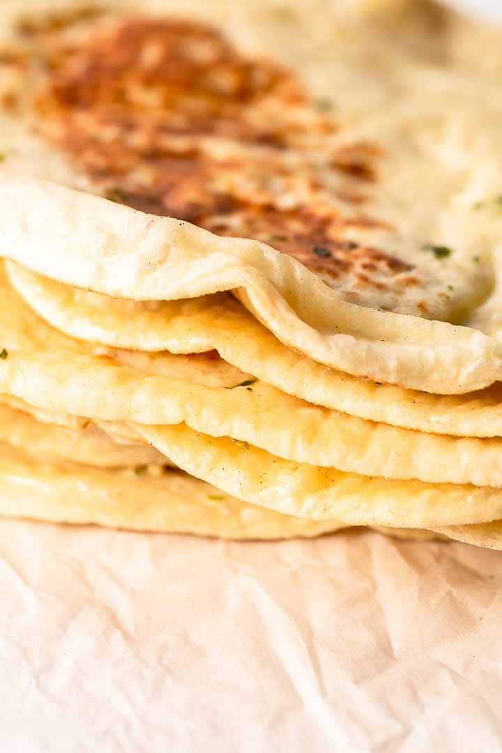 Want to make soft, fluffy naan bread? Try this easy naan bread with garlic recipe. Just as good as any restaurant naan. Serve with your favorite curry. Visit thetortillachannel.com for the full recipe #thetortillachannel #garlicnaan #naanwithgarlic #naan #naanbread #garlicnaanrecipe