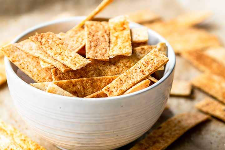 These baked tortilla strips are the best! Use as topping on your soup, chili or salad. You can also serve them as a snack. They are easy to make and super cheap. Visit thetortillachannel.com for the full recipe #thetortillachannel #tortillastrips #bakedtortillastrips #tortillasnack